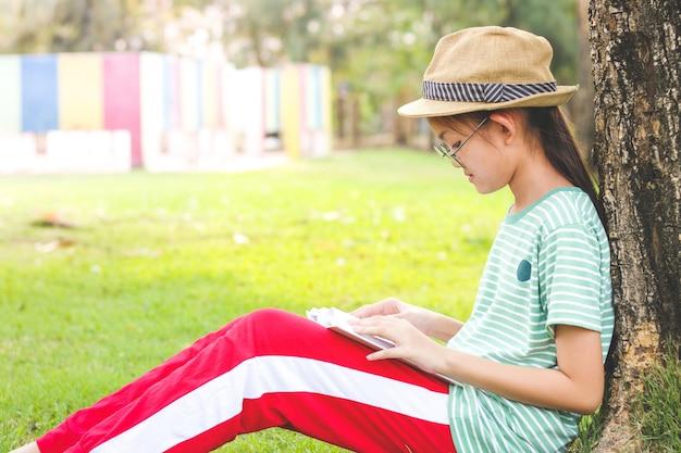 Aziatisch schoolmeisje met hoed op. ze zat een boek te lezen onder een grote boom. Premium Foto
