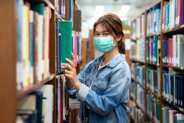 Aziatisch universitair studentenmeisje dat gezichts beschermend medisch masker draagt voor bescherming Premium Foto