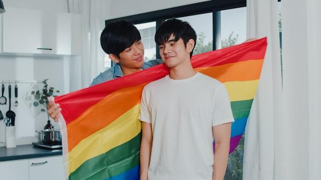 Aziatisch vrolijk paar die en ruimte zich thuis koesteren. jonge knappe lgbtq + mannen die gelukkig kussen, ontspannen rust samen doorbrengen romantische tijd in moderne keuken met regenboogvlag in huis in de ochtend. Gratis Foto
