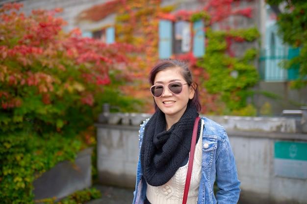 Aziatisch vrouwen toothy het glimlachen gezicht met de kleurrijke achtergrond van het bladerenpark Premium Foto