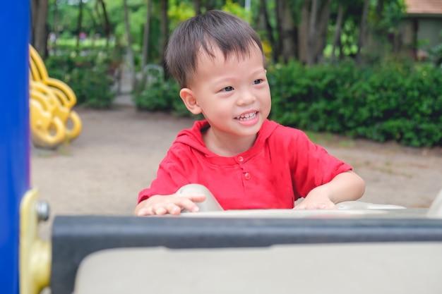 Aziatische 3-4 jaar oude peuter jongenskind plezier klimmen op kunstmatige keien in speeltuin in het park Premium Foto