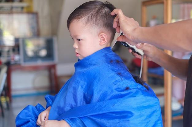 Aziatische 3 jaar oud peuterbaby jongenskind dat een kapsel krijgt bij de kapper van de kapper Premium Foto