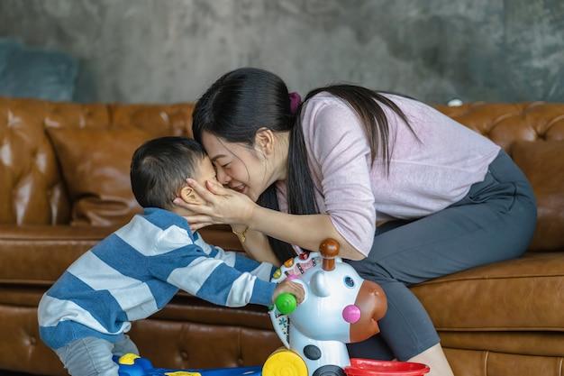 Aziatische alleenstaande moeder en zoon spelen samen met speelgoed wanneer ze in een loft wonen voor zelfstudie Premium Foto