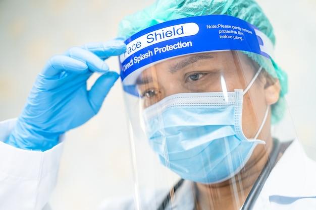 Aziatische arts die gezichtsscherm en pbm-pak draagt om het covid-19 coronavirus te beschermen. Premium Foto