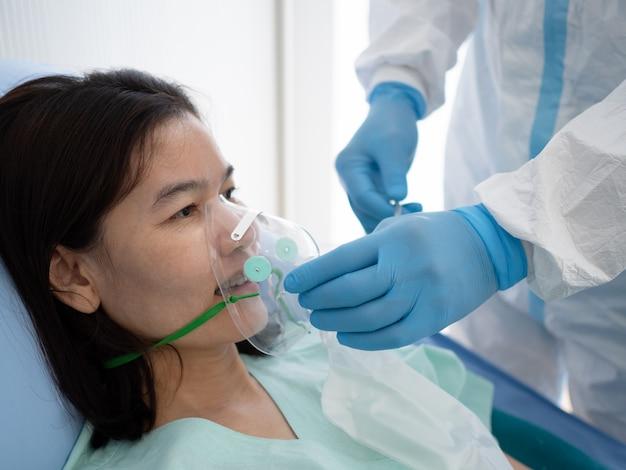 Aziatische arts draagt ppe-pakbehandeling en gebruikt zuurstofmasker of noodinhalatiemasker met coronavirus-geïnfecteerde patiënt in quarantainekamer met negatieve druk. medisch en gezondheidsconcept. Premium Foto