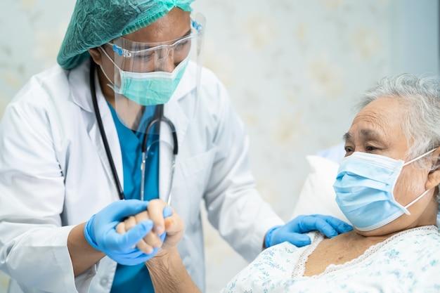 Aziatische arts met gezichtsscherm en pbm-pak nieuw normaal om te controleren of de patiënt de veiligheid van de infectie covid-19 coronavirus-uitbraak op de quarantaineverpleegkundige ziekenhuisafdeling beschermt. Premium Foto