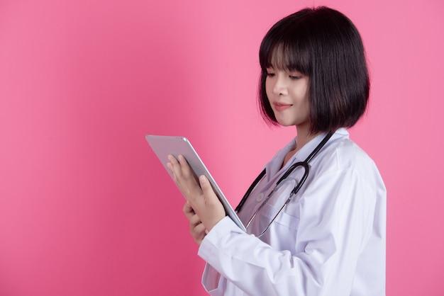 Aziatische arts vrouw met witte laboratoriumjas over roze Gratis Foto