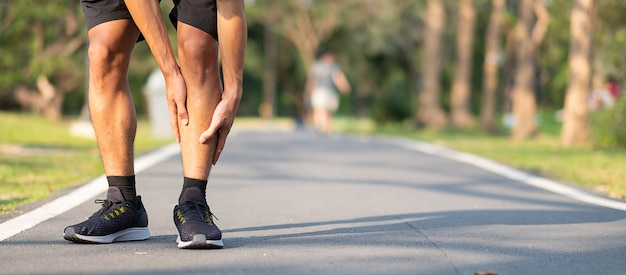 Aziatische atleet met kuitpijn en probleem na rennen en sporten buiten Premium Foto