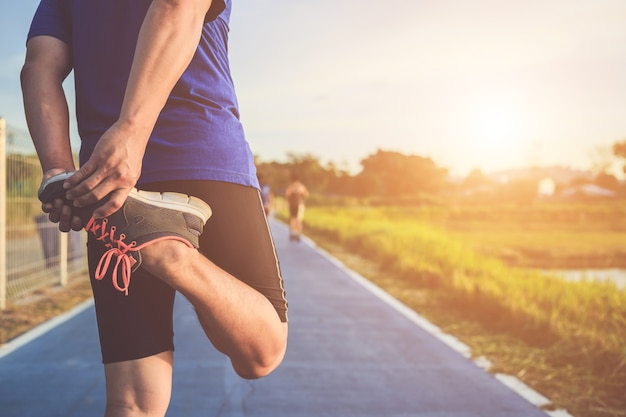 Aziatische atleet warmt zijn lichaam op voordat hij op weg begint te rennen Premium Foto