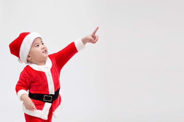Aziatische babyjongen in een kerstmiskostuum santa claus die vingers richten en lachen geïsoleerd op wit, gelukkig en glimlach Premium Foto