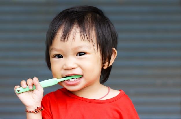 Aziatische babymeisjespraktijk om haar tanden te poetsen. Premium Foto