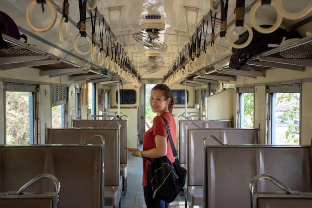 Aziatische backpacker binnen de openbare trein met lege zetels op vakantie Premium Foto