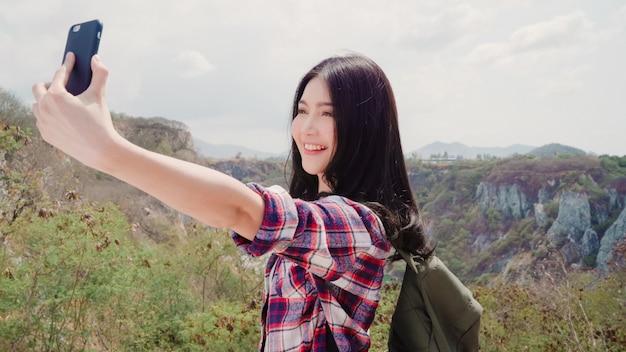 Aziatische backpacker vrouw selfie op de top van de berg, jonge vrouwelijke gelukkig met behulp van mobiele telefoon nemen selfie genieten van vakantie op wandel-avontuur. Gratis Foto