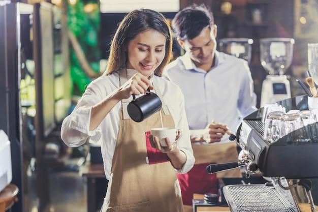 Aziatische barista die kop van koffie, espresso met latte of cappuccino voor klantenorde voorbereiden in koffiewinkel Premium Foto