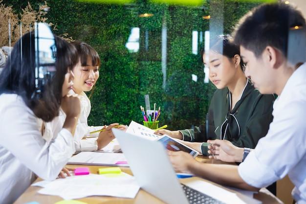 Aziatische bedrijfsmensen die aan project en brainstorming in bureau bij nacht samenwerken Premium Foto