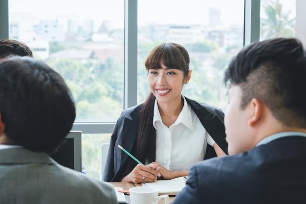 Aziatische bedrijfsvrouw die aan het team van de collegavergadering op kantoor luisteren de presentatie van de bedrijfs teamvergadering, conferentie plannings bedrijfsconcept Premium Foto