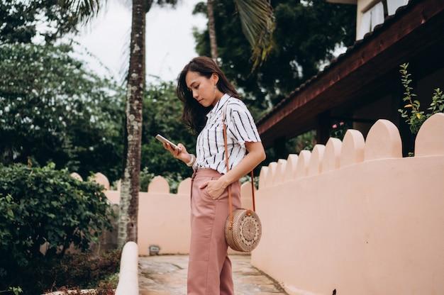 Aziatische bedrijfsvrouw op een vakantie die op telefoon spreekt Gratis Foto