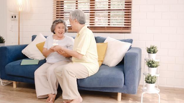 Aziatische bejaarde paar man met cake vieren vrouw verjaardag in de woonkamer thuis. het japanse paar geniet liefde van ogenblik samen thuis. Gratis Foto
