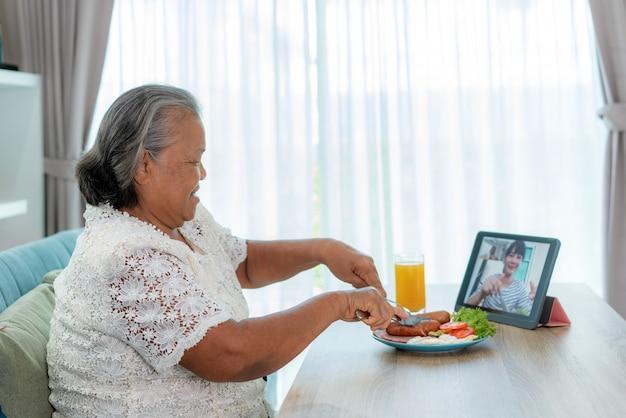 Aziatische bejaarde virtuele happy hour ontmoeting en eten online samen met haar dochter Premium Foto