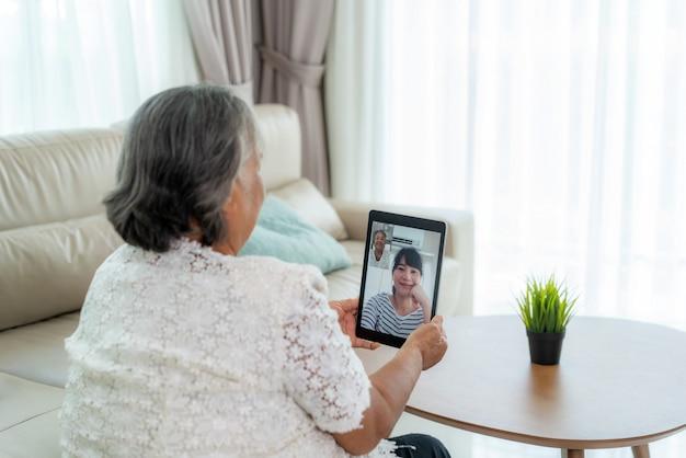 Aziatische bejaarde virtuele happy hour vergadering en online praten samen met haar dochter Premium Foto