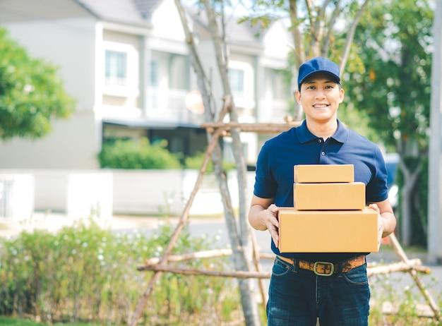 Aziatische bezorgen man in blauwe uniforme pakketdoos Premium Foto