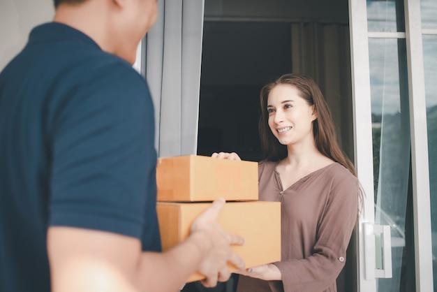 Aziatische bezorgen man in blauwe uniforme verpakkingsdoos Premium Foto