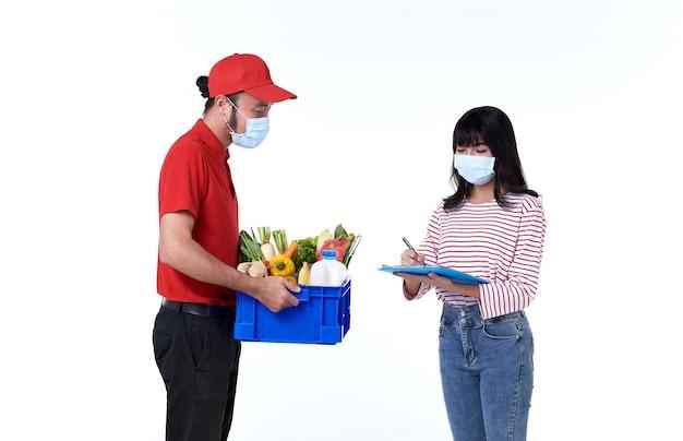Aziatische bezorger met gezichtsmasker in rood uniform met boodschappen doos met voedsel Gratis Foto