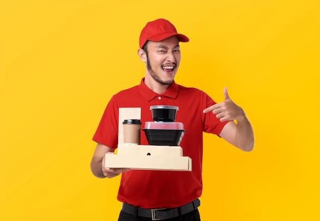 Aziatische bezorgmens die in rood uniform draagt ?? de doos van de holdingslunch en afhaalkoffie die over gele ruimte wordt geïsoleerd Gratis Foto