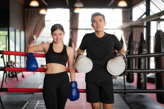 Aziatische bokser sport meisje en trainer op zoek glimlach terwijl leunde op zwart rode touwen op boksring Premium Foto