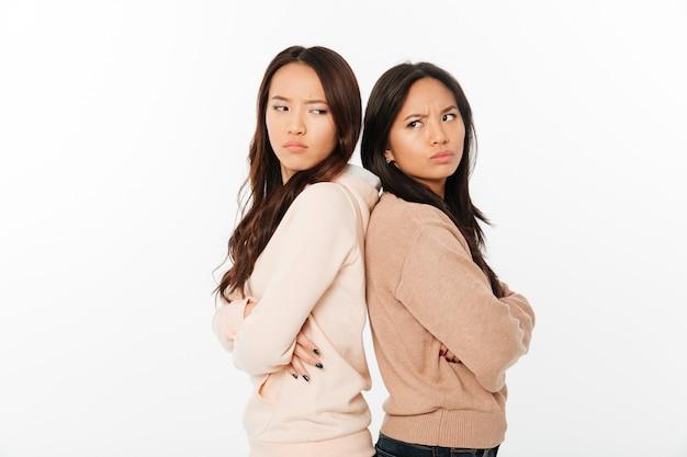 Aziatische boze dameszusters die zich geïsoleerd bevinden Gratis Foto