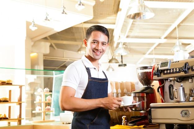 Aziatische coffeeshop - barista presenteert koffie Premium Foto