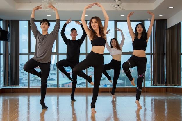 Aziatische dansers die zich op één voet bevinden Gratis Foto