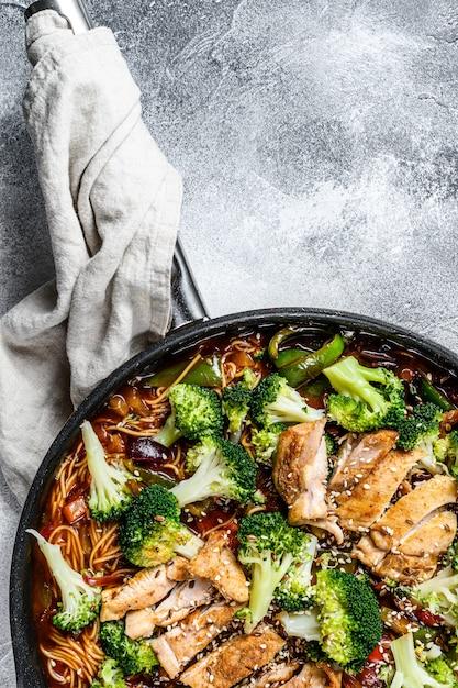 Aziatische einoedels met groenten en vlees bij het koken van pan. grijze achtergrond. bovenaanzicht ruimte voor tekst Premium Foto
