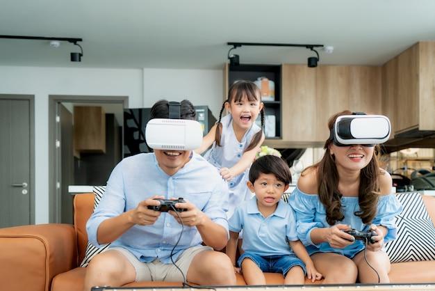 Aziatische en gelukkige familie thuis op de bank in de woonkamer met plezier met het spelen van spelletjes Premium Foto