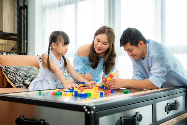 Aziatische familie brengt tijd door in de speelkamer met meisje spelen Premium Foto