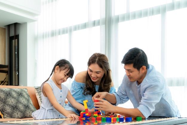Aziatische familie brengt tijd door in de speelkamer met vader, moeder en dochter met speelgoed op kamer Premium Foto