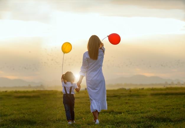 Aziatische familie. familie met ballonnen in de wei achter de zonsondergang. aziatische familie Premium Foto