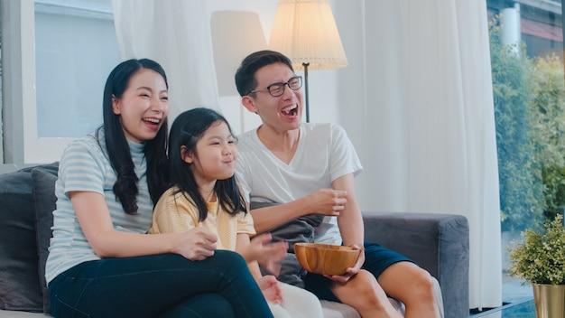 Aziatische familie geniet van hun vrije tijd ontspannen samen thuis. lifestyle vader, moeder en dochter kijken 's nachts samen tv in de woonkamer in een modern huis. Gratis Foto