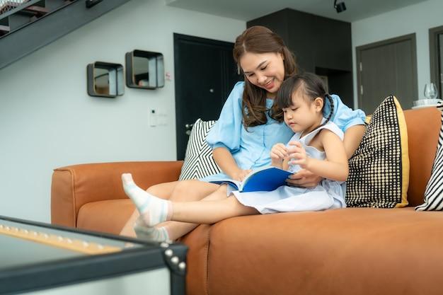 Aziatische familie met moeder en haar dochter die het boek van het sprookjeverhaal op bank thuis lezen Premium Foto