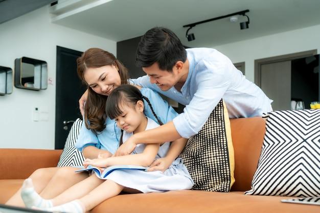 Aziatische familie met vader, moeder en haar dochter die het boek van het sprookjesverhaal op bank thuis lezen Premium Foto