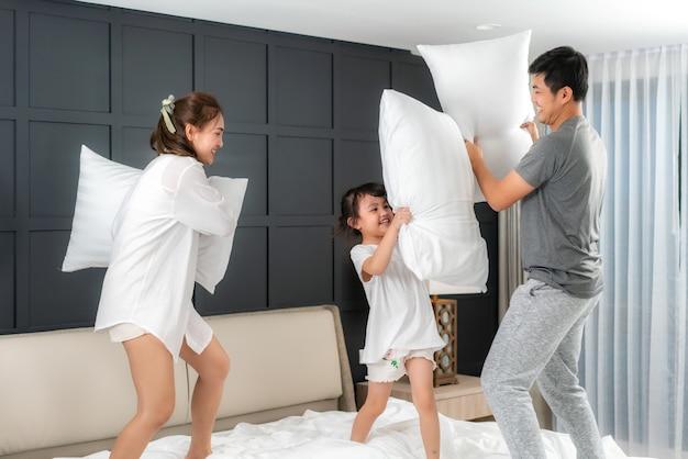 Aziatische familie vechten met kussens Premium Foto