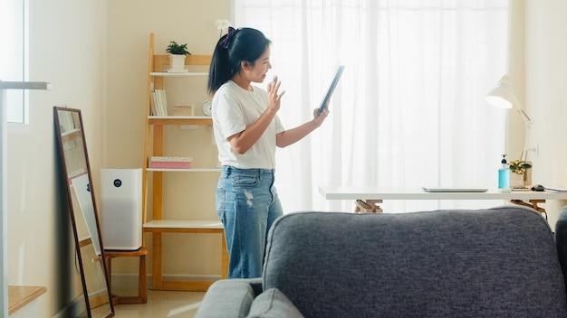 Aziatische freelance bedrijfsvrouwen vrijetijdskleding die videoconferentie van de tablet de werkende vraag met klant in werkplaats in woonkamer van huis gebruiken wanneer de sociale afstand thuis blijft en zelf quarantainetijd. Gratis Foto