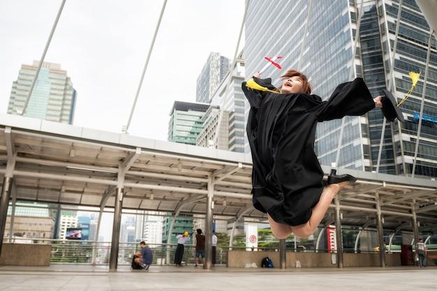 Aziatische gediplomeerde vrouw in togasprong met diploma Premium Foto