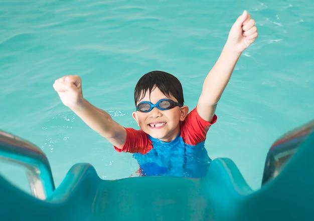 Aziatische gelukkige jong geitje speelschuif in zwembad Gratis Foto
