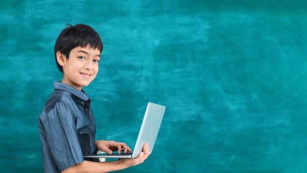 Aziatische gelukkige laptop van de schooljongenholding Premium Foto