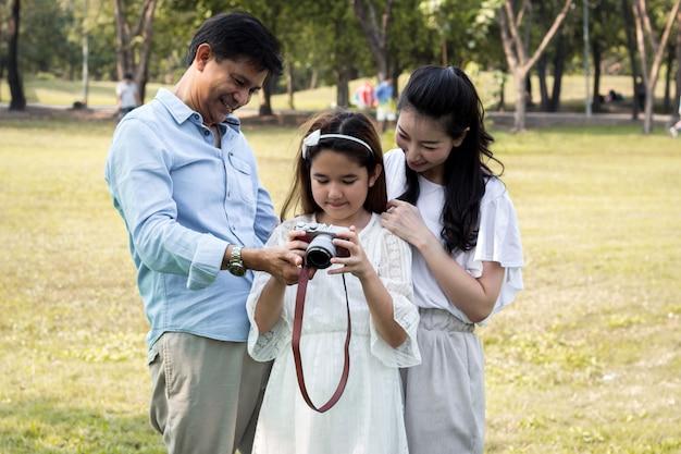 Aziatische gezinnen kijken naar foto's van hun camera's. Premium Foto