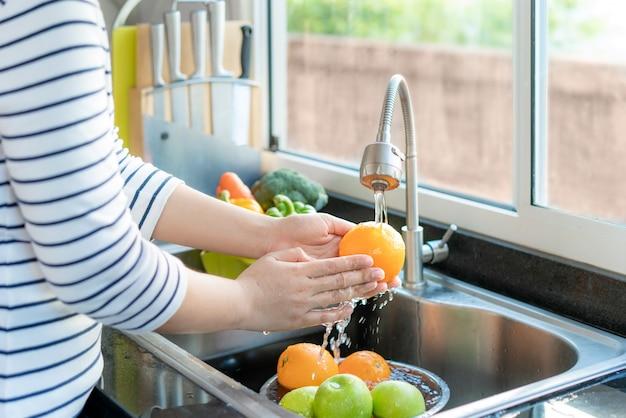 Aziatische gezonde vrouw die een sinaasappel en ander fruit boven gootsteen wast en een groente / fruit met water schoonmaakt om de kans op besmetting covid-19 te elimineren. Premium Foto