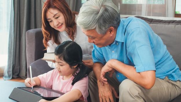 Aziatische grootouders en kleindochter videogesprek thuis. hogere chinees, opa en oma gelukkig met meisje die mobiel telefoonvideogesprek met behulp van die met papa en mamma spreken die in woonkamer thuis liggen. Gratis Foto