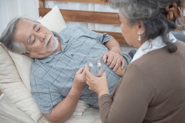 Aziatische hogere mens die medicijnen en drinkwater nemen terwijl thuis op laag, gezondheid en geneeskundeconcept liggen met exemplaarruimte. Premium Foto