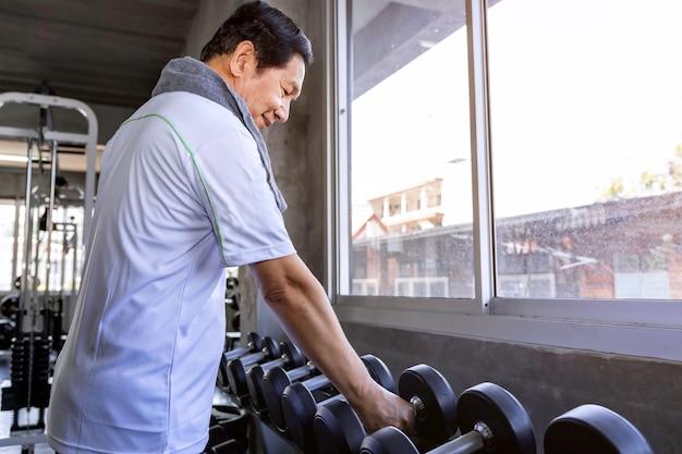 Aziatische hogere mens in sportkleding opleiding met domoor bij gymnastiek. Premium Foto